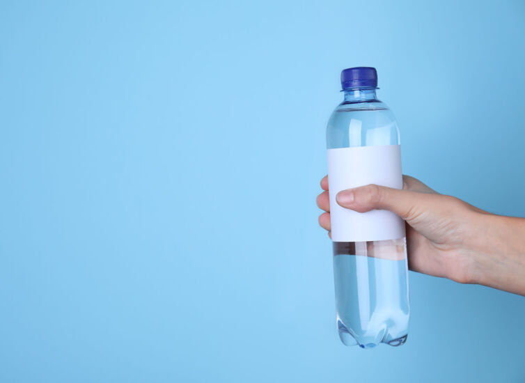 Woman holding plastic bottle with soda water on light blue backg